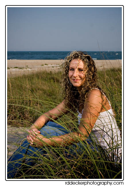 High on a dune and nestled in the sea oats, Tina enjoys a day at Atlantic Beach.
